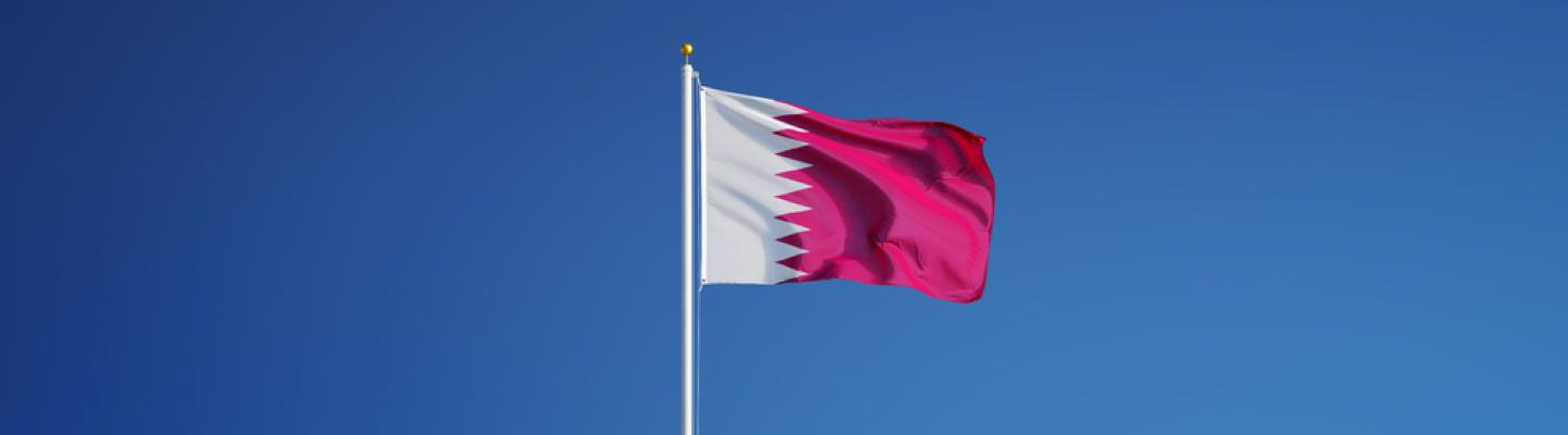 Flag of Qatar against blue sky