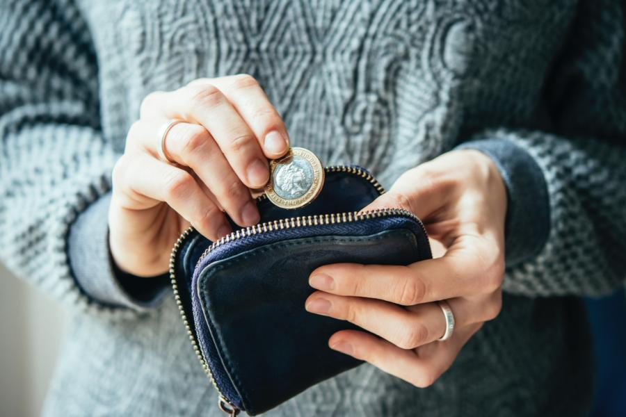 Woman putting two pounds in her purse